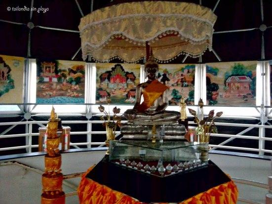 Buda plateado rodeado de pinturas tradicionales